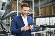 Smiling businessman using cell phone in a factory - BSZF01167
