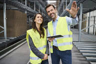 Colleagues wearing reflective vests with tablet in factory - BSZF01182