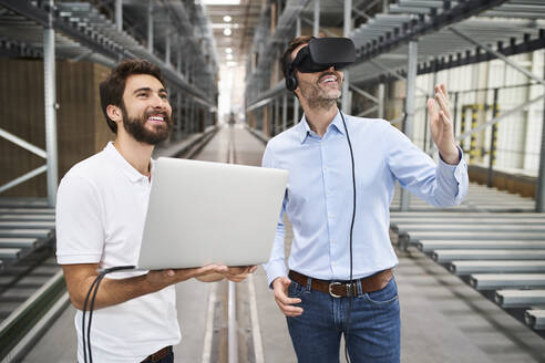 Man with laptop and businessman wearing VR glasses in factory - BSZF01185