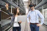 Businesswoman with laptop and businessman wearing VR glasses in factory - BSZF01188