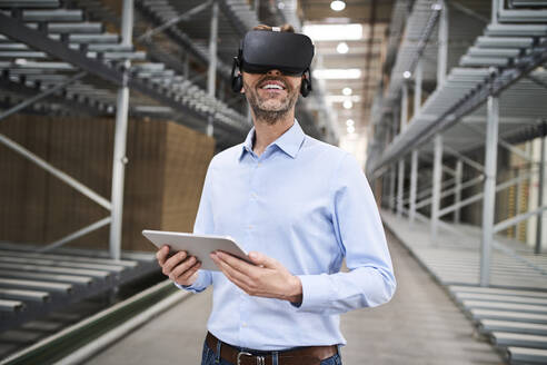 Businessman with tablet wearing VR glasses in factory - BSZF01191