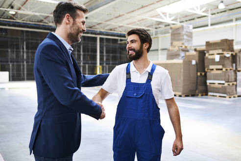 Businessman and worker shaking hands in a factory - BSZF01242
