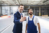 Happy businessman and worker in a factory - BSZF01245