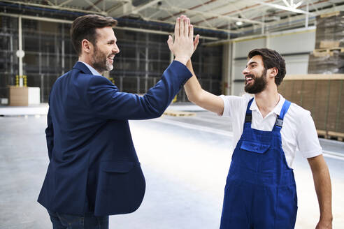 Happy businessman and worker high fiving in a factory - BSZF01251