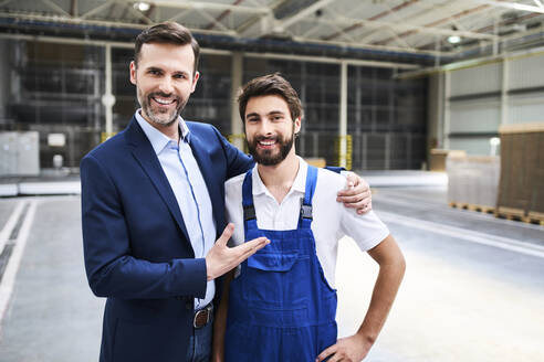 Portrait of happy businessman and worker in a factory - BSZF01254