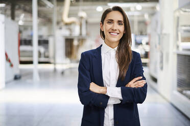 Portrait of smiling businesswoman in a factory - BSZF01272