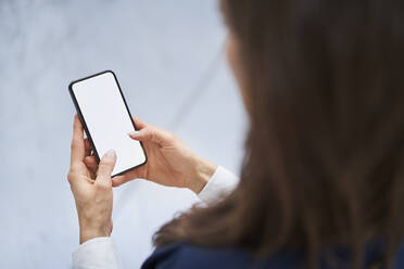 Close-up of businesswoman holding cell phone in factory - BSZF01275