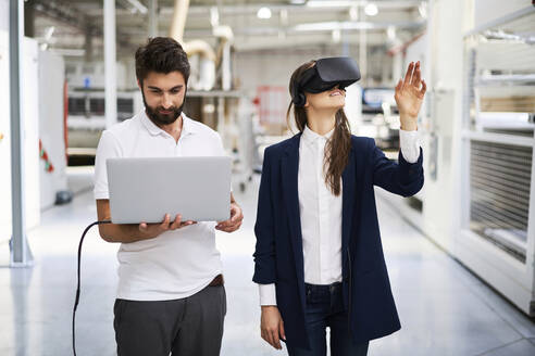 Man with laptop and businesswoman wearing VR glasses in factory - BSZF01278