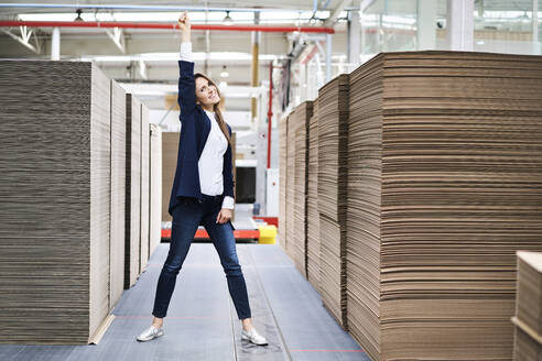 Portrait of excited businesswoman in factory warehouse - BSZF01287