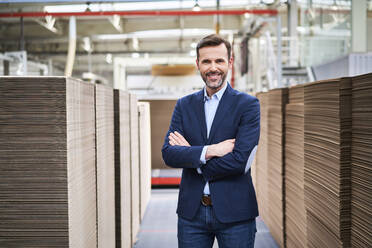 Portrait of smiling businessman in factory warehouse - BSZF01290