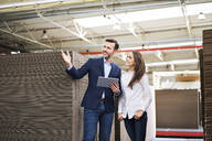 Businessman with tablet talking to woman in factory warehouse - BSZF01293