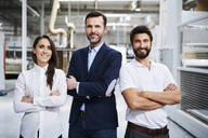 Portrait of confident businessman and employees in a factory - BSZF01308