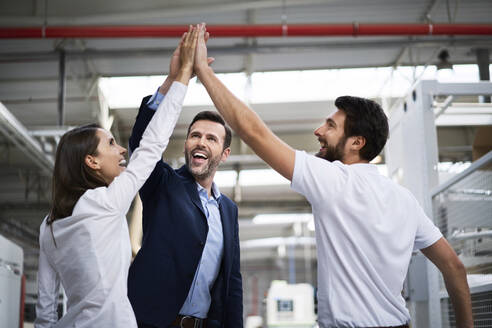 Happy businessman and employees high fiving in a factory - BSZF01311
