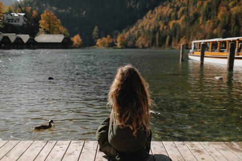 Deutschland, Bayern, Königssee, Portrait einer jungen Frau, kein Gesicht, sitzend mit dem Rücken - OGF00087