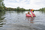 Young woman floating on a lake in a pink flamingo floating tire - GUSF02279