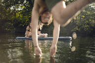 Young man diving into lake, young women on paddleboard warching - GUSF02300