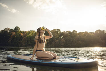 Young woman with tatto kneeling on paddleboard, using VR goggles - GUSF02306