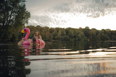 Friends having fun on a lake on a pink flamingo floating tire - GUSF02324