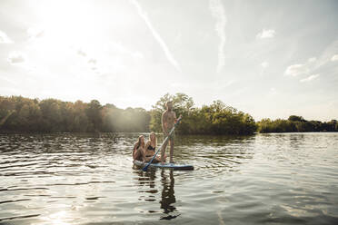Friends enjoying summer on the lake, paddling on a paddleboard - GUSF02339