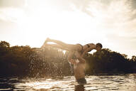 Young man lifting woman out of the lake water - GUSF02345