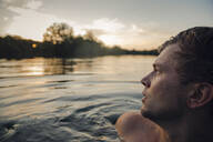 Young man swimming in lake, watching sunset - GUSF02357