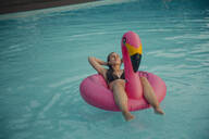 Young woman relaxing on a pink flamingo floating tire - GUSF02369