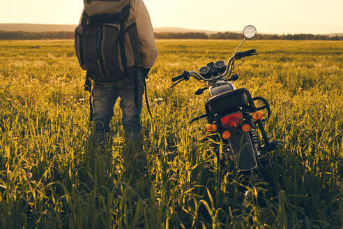 Mari man standing in field with motorcycle - BLEF13061