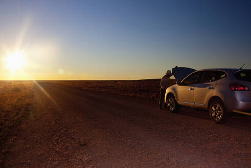 Person opening hood of car on remote road, Grand Canyon National Park, Arizona, United States - BLEF13076