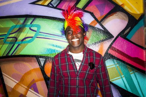 Black man in colorful wig smiling near graffiti wall - BLEF13131