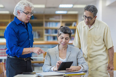 Teacher helping adult students use digital tablet in library - BLEF13323