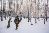 Mixed race man walking in snowy forest - BLEF13389