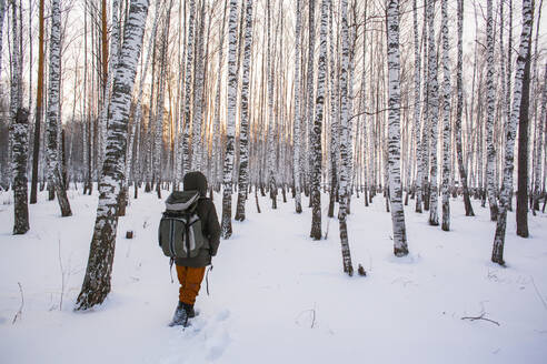 Mixed race man walking in snowy forest - BLEF13389