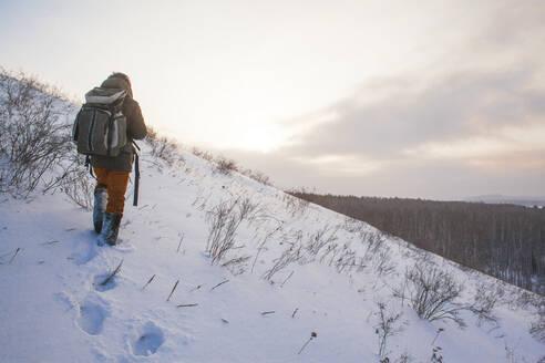 Mixed race man walking on snowy hillside - BLEF13392