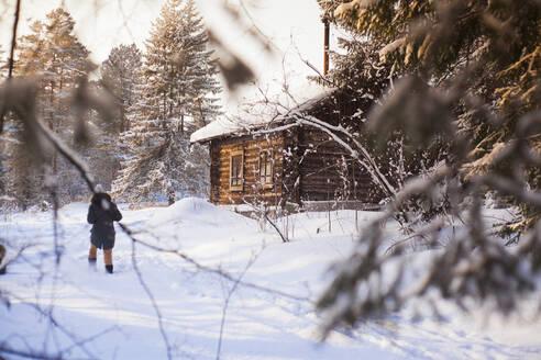 Caucasian woman walking near log cabin in snowy forest - BLEF13404