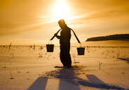 Silhouette of Mari man carrying buckets on traditional yoke in snowy field - BLEF13407