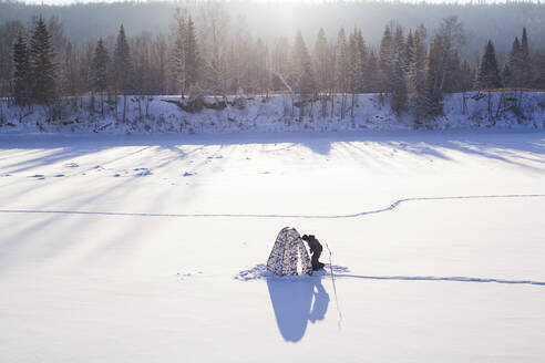 Mari man setting up tent in snowy field - BLEF13410
