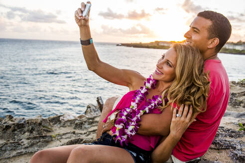 Couple taking cell phone photograph on beach - BLEF13446