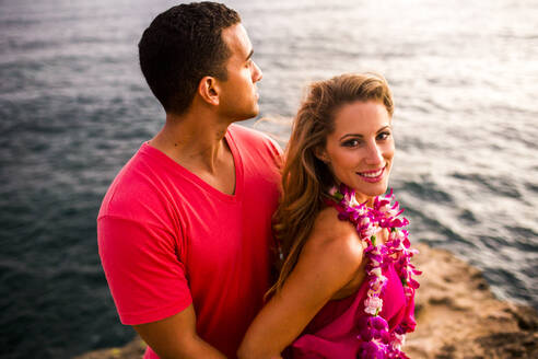 Smiling couple hugging on rocks over ocean - BLEF13449