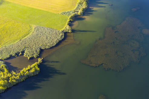 Scenic drone view of Lake Riegsee by green land at Bavaria, Germany - LHF00660