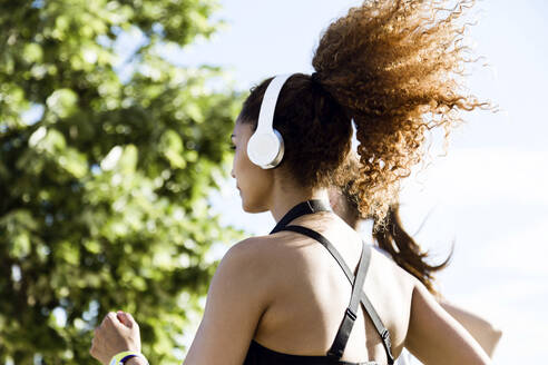 Sporty woman with headphones running - JSRF00483