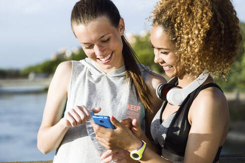 Portrait of two fit and sporty young women using mobile phone in the park. - JSRF00492