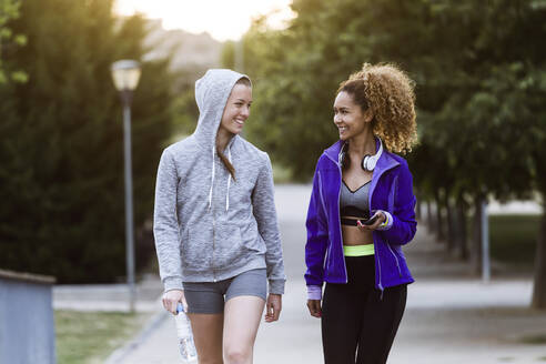 Two smiling sporty young women walking in park after workout - JSRF00501