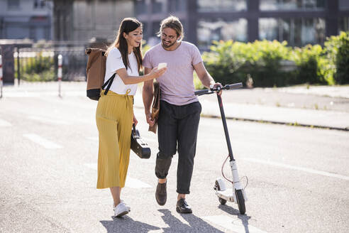 Young couple with electric scooter and smartphone walking on the street - UUF18386