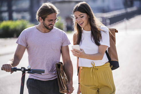 Young couple with electric scooter and smartphone on the street - UUF18389