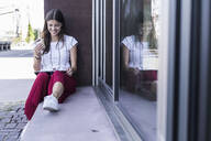 Young woman sitting on windowsill at a building using a tablet - UUF18425
