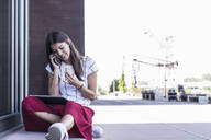 Young woman sitting on windowsill at a building talking on cell phone - UUF18428