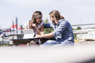 Happy young couple with tablet in a beer garden - UUF18449