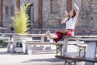 Happy young woman sitting on table in a beer garden using cell phone - UUF18458