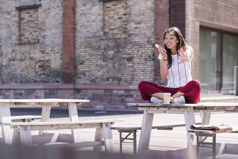 Young woman sitting on table in a beer garden using cell phone - UUF18461