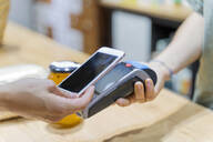 Customer paying cashless with smartphone in a shop - AFVF03611